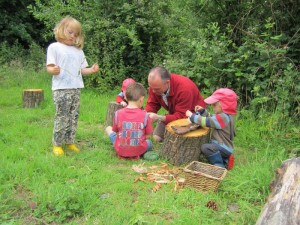 A father helping the children (Parents as partners) at The Forest School, Strawberry Patch Nursery, Norfolk